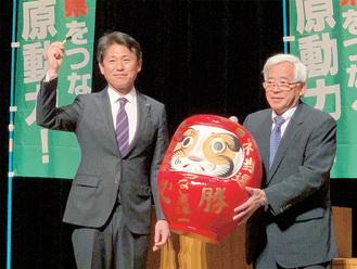 だるまに目入れをする綱嶋氏(左)