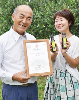 オリーブ畑で笑顔の山田さん(左)とスタッフ