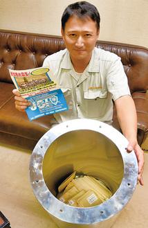 タイムカプセルを開封する川崎さん、右手に持つのは当時のチラシ