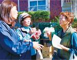 買い物客と立ち話をする佐藤支店長(左)