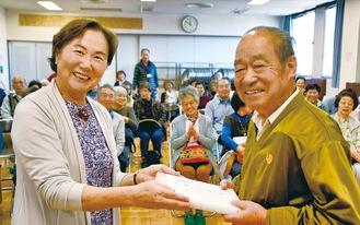 いた委員長の高野さん(左)から記念品を受け取る栗原さん(右)