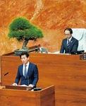 本会議場で一般質問をするつなしま洋一(左)