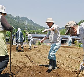 大塚さん(中央)の指導の下作業を進める参加者