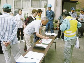 地図や避難者名簿を確認し状況を確認する参加者