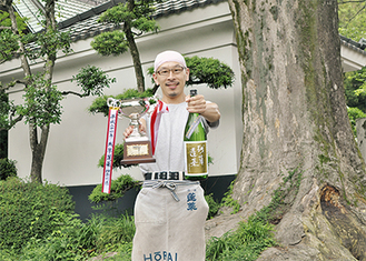 受賞酒とトロフィーを持つ大矢俊介さん