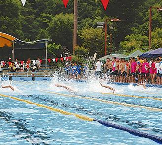 水しぶきを上げ泳ぐ自由形の選手たち