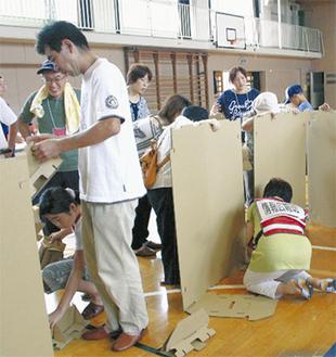 体育館で間仕切り設置をする参加者