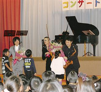 演奏終了後、児童から花束を受取る3人
