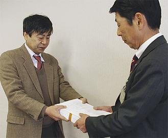 署名を渡す鈴木代表(左)