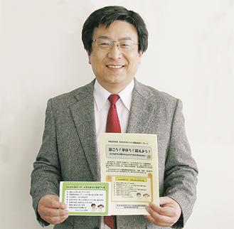 冊子を手にする村立緑小学校の湯浅誉啓教頭