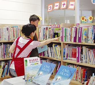 返却された本を書架に戻す小学生