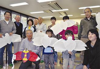 制作中の凧を手に笑顔の参加者たち