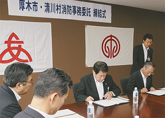 締結書に署名する大矢村長と小林市長