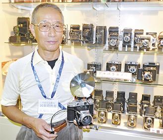 カメラを手にする大塚さん。展示期間中は休館日をのぞいて会場に常駐し、展示品の説明なども行っている