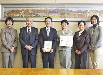 小野澤町長(写真中央)へブックナビを寄贈する啓発資料作成班の西村代表(中央右)とメンバーら