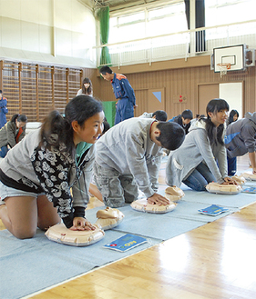 胸骨圧迫を学ぶ児童たち
