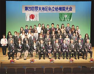 永年勤続表彰の教職員と来賓らで記念撮影(=11月13日、市文化会館小ホール)