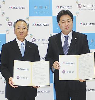協定書を手にする大矢村長(左)と石井支店長