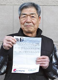 825点を記録したスコア表を手にする山田さん