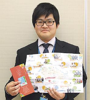 新しいデザインのパンフレットを持つ町職員