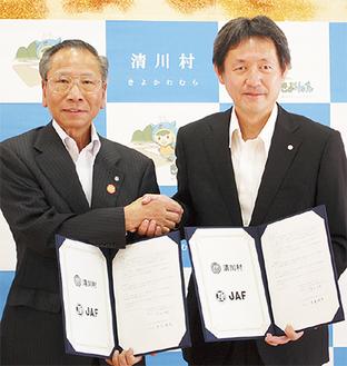 協定書を手にする大矢村長(左)と川喜田事務所長