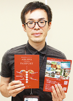 新ガイドブックの「AIKAWA TOWN PASSPORT」を手にする町職員