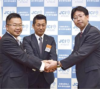 握手をする(左から)小澤理事長、長島部長、北村会長