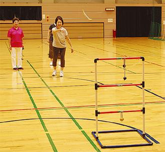 ラダー(ハシゴ)にひも付きのボールを引っ掛ける「ラダーゲッター」に挑戦する参加者