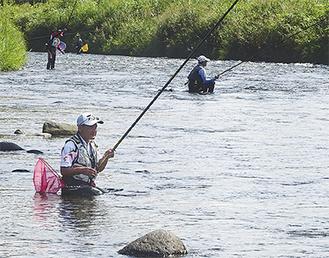 腰まで水につかり鮎を追う参加者たち