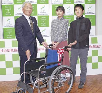車椅子を寄贈する福祉委員の片山さん(中央)、邨松君(右)と、受け取る萩原会長(左)