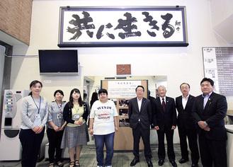 金澤さんの作品が設置された本庁舎1階ホール。小野澤町長と町社協職員らによる記念撮影