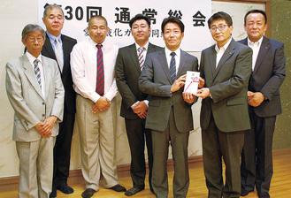 小野澤総務部長(右から2人目)に目録を手渡す熊坂理事長(右から3人目)