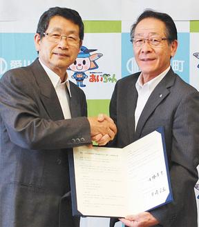 協定書を手にする柴崎理事長(左)と小野澤町長