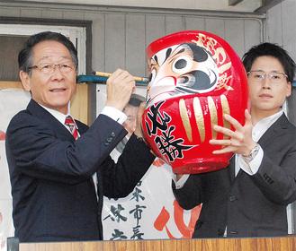 18日の当選報告会でだるまに目を入れる小野澤氏