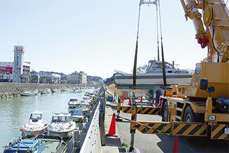 クレーンで不法係留船が引き上げられた。撤去費用は1隻約60万円という