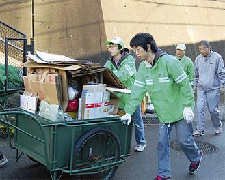 リアカーを引きながら、資源ごみの回収を手伝う内田さんと奥津さん(=先月16日)。若い力が頼りになるという