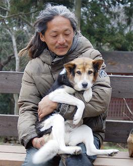菊池さんに抱かれるミックス犬のモチ