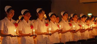 ロウソクの明かりを手にして看護師としての誓いをたてる(=今月14日、神奈川歯科大学大講堂)
