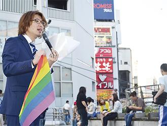 性的マイノリティを象徴するレインボーフラッグを持ち通行人に呼びかける藤野英明市議(=17日、横須賀中央Yデッキ)