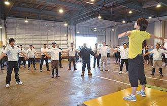魚市場で開かれた出張教室。約60人の従業員が正しいラジオ体操のレクチャーを受けた