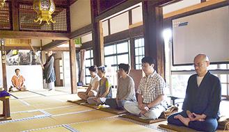 開け放たれた本堂の中で座禅を組む参加者