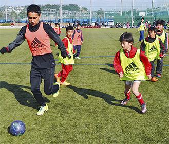ボールを追いかける谷口選手(鴨居SC出身)と子どもたち