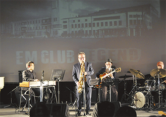 スクリーンに映し出されたEMクラブを背に演奏する「中村誠一グループ」