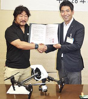 握手を交わす吉田市長と堂城川さん(左)