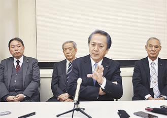 出馬会見で上地氏(中央)。後列は支持を表明した3会派の議員