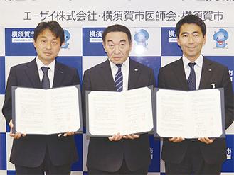 会見には「エーザイ」の藪根氏(左)や医師会の遠藤会長(中央)らが出席