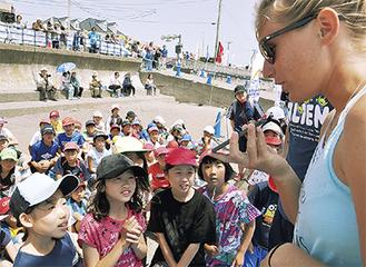 翻訳アプリを介して海外選手と会話を楽しむ児童ら