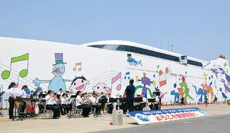 夏を思わせる日差しの中で三浦学苑の吹奏楽部が歓迎演奏
