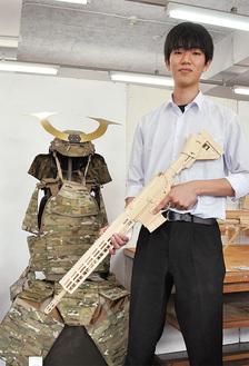 ポーランド製の銃を再現した「木銃」を手に。背後にある布製の甲冑も小松君が手掛けた