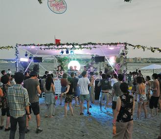 夕日が沈む黄昏時。猿島ビーチに設けられたDJブースを囲むように若者が踊る